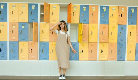 An Image of How to keep your kids active this summer when school's out. The girl is wearing a summer dress with vacant lockers at the back